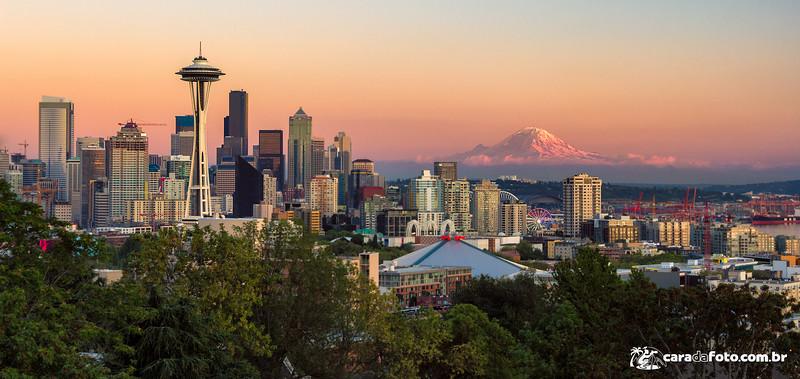 """Estava com a minha namorada fazendo uma roadtrip pelos Estados Unidos, e essa cidade (Seattle) era a última do itinerário de 20 e tantos dias na estrada.<br /> <br /> Eu já tinha dirigido quase 7 mil quilômetros nos últimos 20 dias, então imagina o nível do MEU combustível.<br /> <br /> Pois bem, o dia dessa foto foi o mesmo que chegamos na cidade. Fomos corremos para o hotel deixar as tranqueiras todas para procurar algum lugar bacana e curtir o pôr do sol.<br /> <br /> A recepcionista foi super gente boa e apontou um lugar """"mega famoso, que provavelmente estará bem lotado de fotógrafos… mas vale a pena! É a melhor vista da cidade"""". Ai eu pensei comigo mesmo """"…sabe nada inocente, vai ser moleza depois desses últimos dias""""...<br /> <br /> Continue lendo para pegar a dica de composição e ver os detalhes técnicos da foto aqui: <a href=""""http://caradafoto.com.br/a-vista-mais-famosa-de-seattle-dica-de-composicao/"""">http://caradafoto.com.br/a-vista-mais-famosa-de-seattle-dica-de-composicao/</a>"""