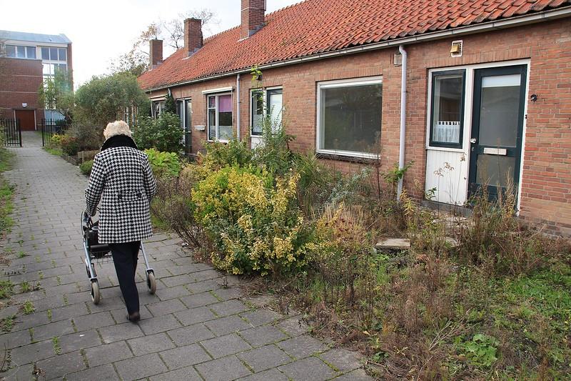 Fotograaf: Jan Sluimer, Oud bewoonster loopt langs haar oude woning die binnenkort wordt gesloopt.