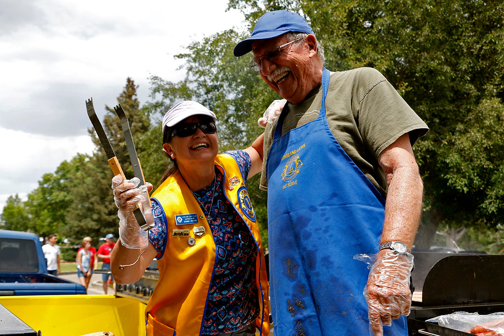 . Jennie Votaw, left, and Carl Bosack, right, joke around as they help with grill duty at North Lake Park in Loveland on Tuesday, July 4, 2017. Votaw and Bosack are a part of the Loveland Lions Club which ran concessions for the Independence Day festivities. (Michelle Risinger/ Loveland Reporter-Herald)