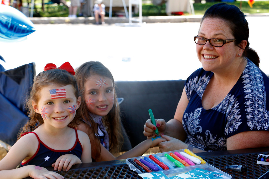 . Maggie Brown, 7, center, and Samara Brown, 5, right, get decked out in Independence Day face paint done by Katie Tyler, left, at North Lake Park on Tuesday, July 4, 2017. (Michelle Risinger/ Loveland Reporter-Herald)