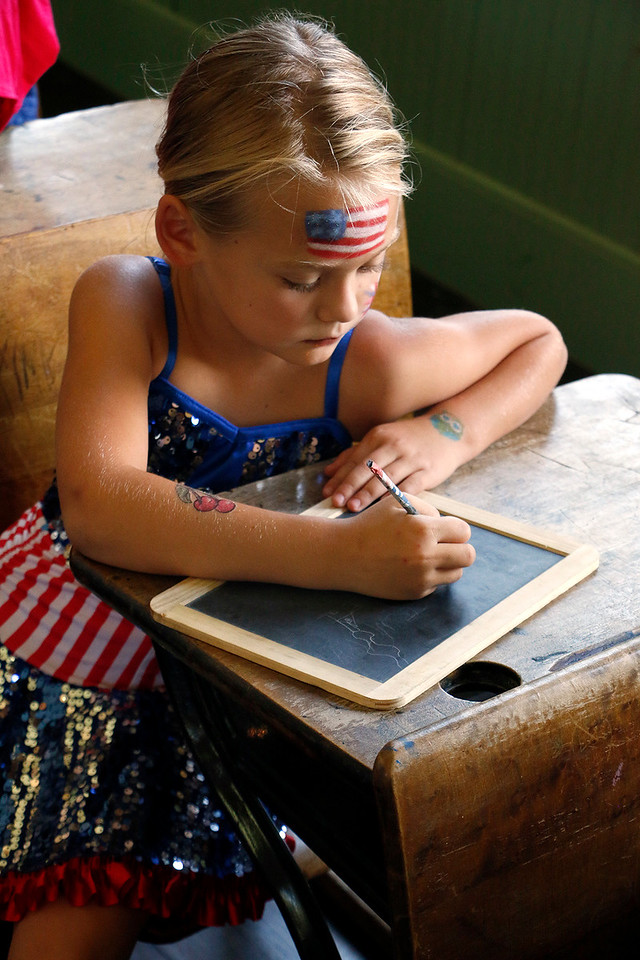 Scarlett Duke, 6, doodles on a slate in the Lone Tree Schoolhouse at North Loveland Park on July 4, 2017. She visited for the history lesson as a part of her family's Independence Day celebrations. (Michelle Risinger/ Loveland Reporter-Herald)