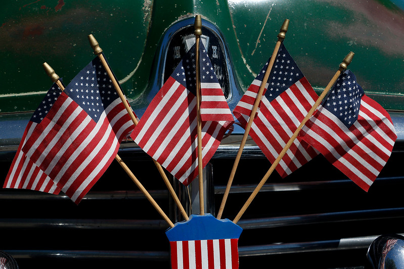 U.S. flags line one of many old fashioned cars at North Lake Park on Tuesday, July 4, 2017 in Celebration of Independence Day. (Michelle Risinger/ Loveland Reporter-Herald)