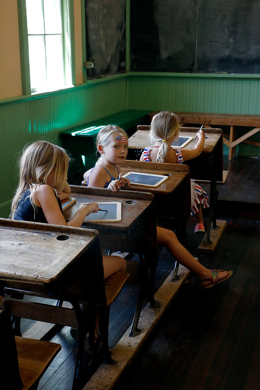 . Grace Duke, 8, right, Scarlett Duke, 6, center, and Taylor Duke, 4, sit in the one room schoolhouse at North Lake Park in Loveland as they learn a history lesson as a part of their Independence Day celebrations, Tuesday, July 4, 2017. (Michelle Risinger/ Loveland Reporter-Herald)