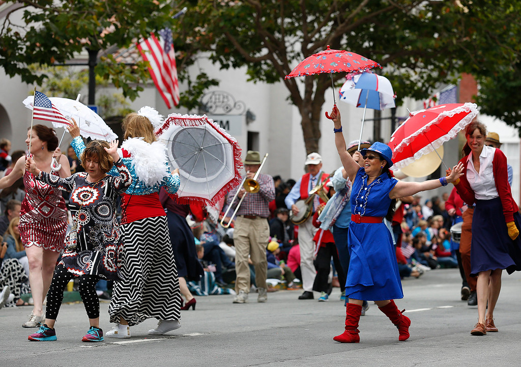 . Thiem Do, center right, of Marina dances with the Monterey Hot Jazz Society and the Dancing Jubulators  strut their way down Calle Principal during the Fourth of July parade in downtown Monterey on Tuesday July 4, 2017. (David Royal for the Monterey Herald)