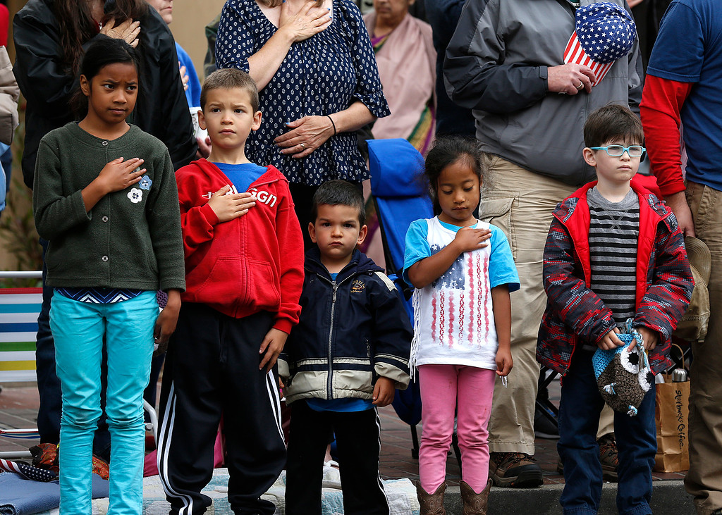 . Youngsters listen to the National Anthem before the start of the Fourth of July parade in downtown Monterey on Tuesday July 4, 2017. (David Royal for the Monterey Herald)