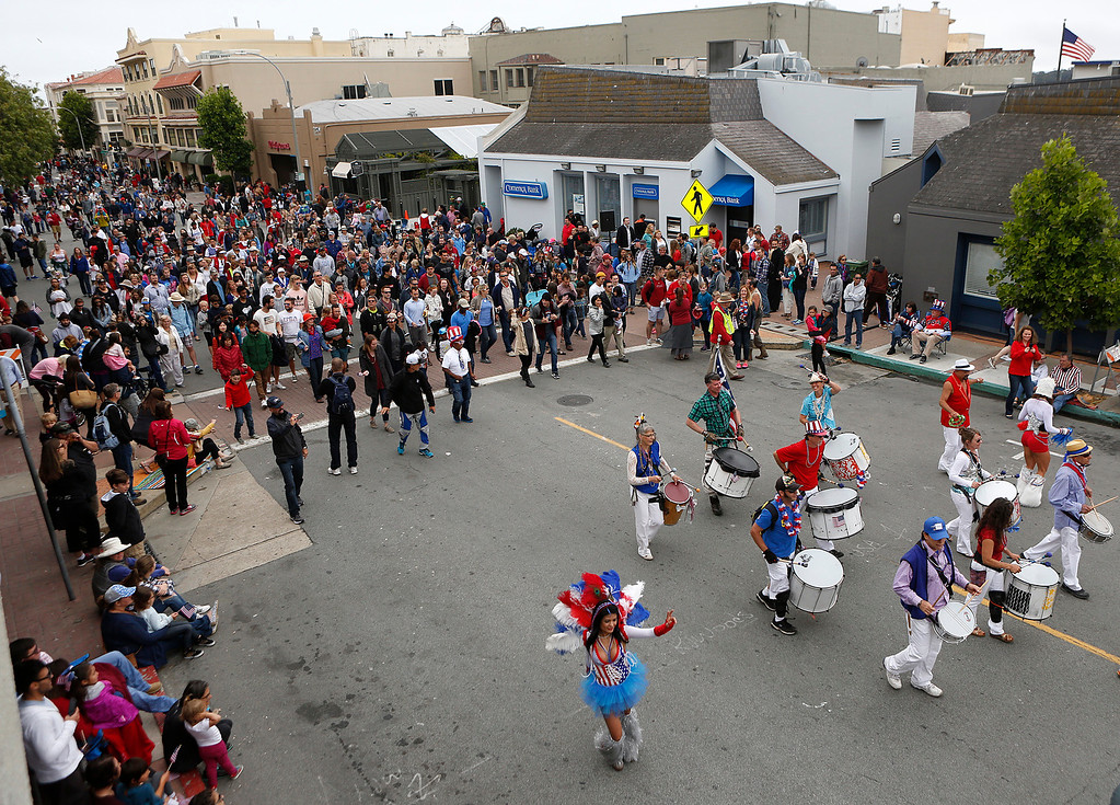 . People follow the Brazilian drumming beat of Samba Legal at the end of the Fourth of July parade in downtown Monterey on Tuesday July 4, 2017. (David Royal for the Monterey Herald)