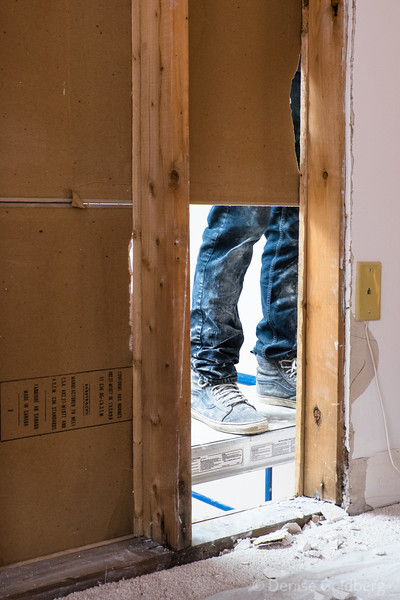 a view from the bedroom into the living room, feet anchored to a scaffold