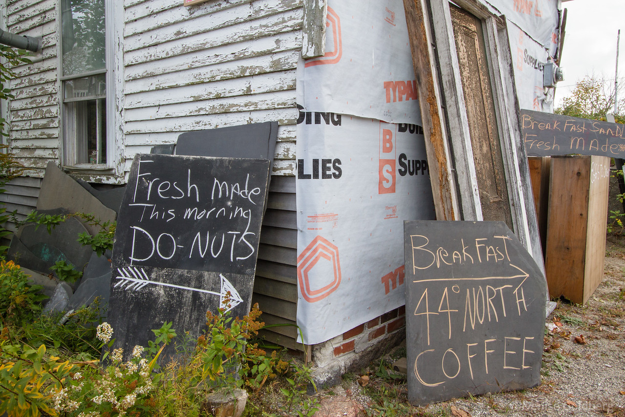 signs against a decaying house advertise for a food truck tucked away in the yard