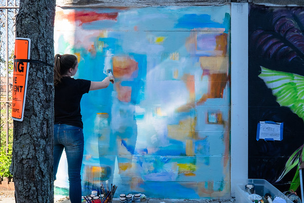an artist at work, creating a mural