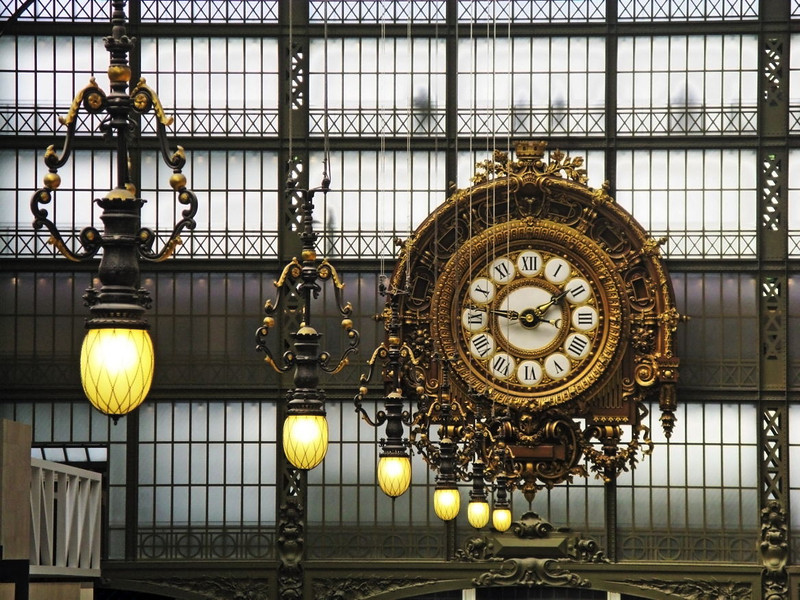 Big clock  and lamps in Musée D'Orsay, note silhouettes of people using corridor behind glass