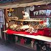 Vendor at the outdoor Xmas market, sells salami, etc.