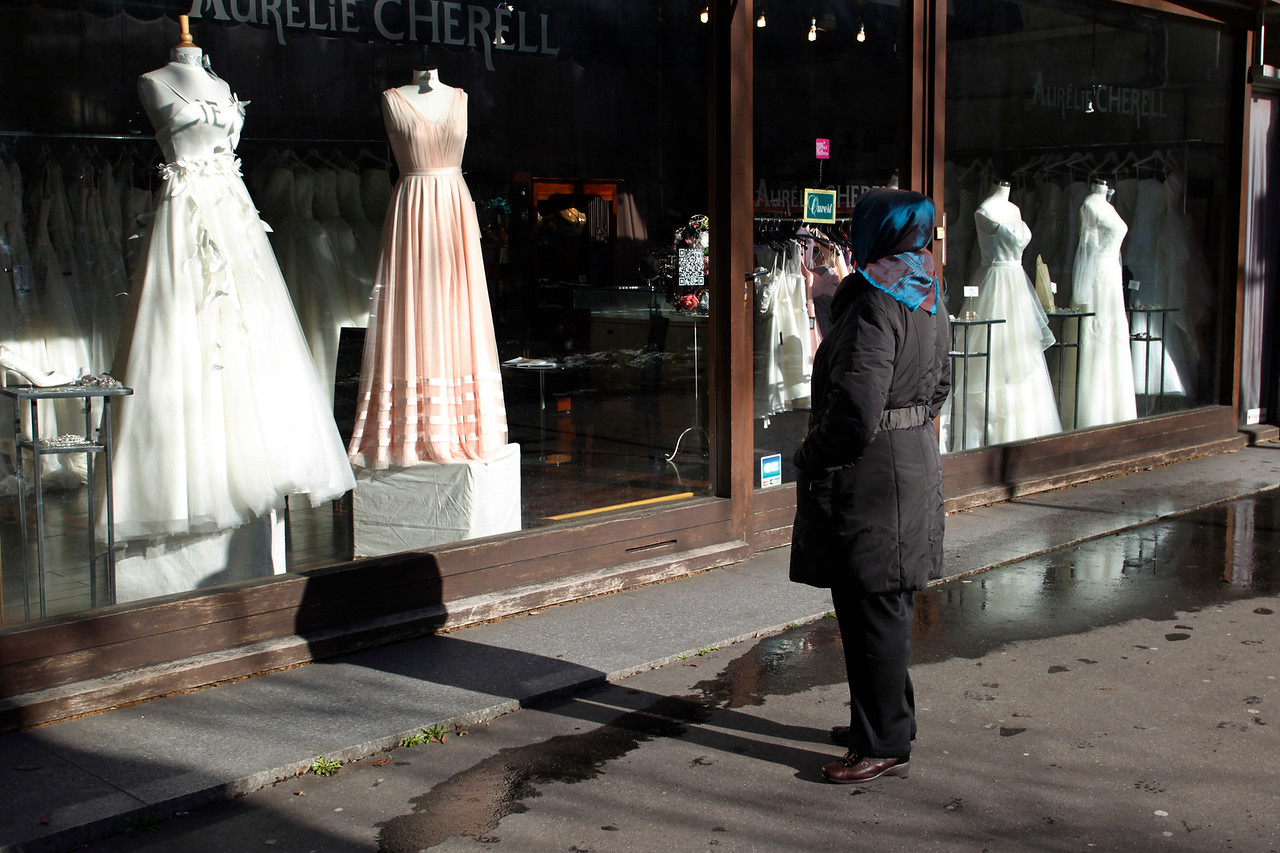 A woman looks at wedding dresses displayed in a shop window in Paris.
