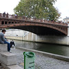 Shoppers sat next to the river to eat some of what they bought.   The bridge is the Pont au Double.