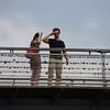 A couple on Passerelle Léopold-Sédar-Senghor considering the love locks