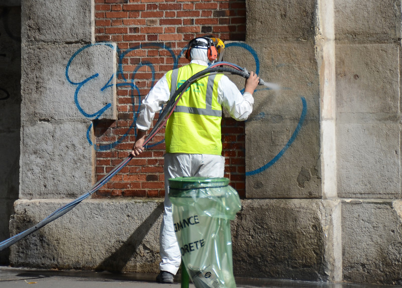 Cleaning the graffiti off the wall.   There's a team that responds quickly in tourist areas.