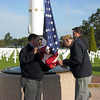 Hoisting the flag at the American Cemetery