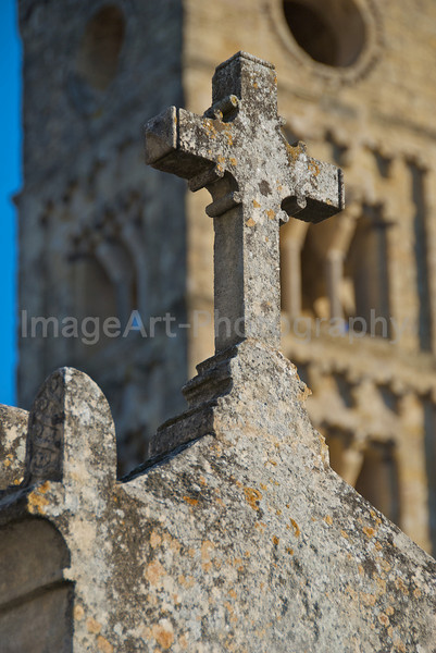 Stone Christian Cross against a Romanesque tower in France