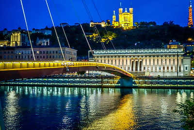 Looking across footbridge passerelle du Palais of Justice on Saone  River to courts and upward to Basilica Notre-Dame de Fourviere