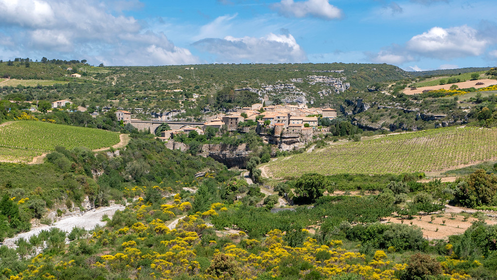 Visiting Minerve France: The town of Minerve from a distance, surrounded by hills.