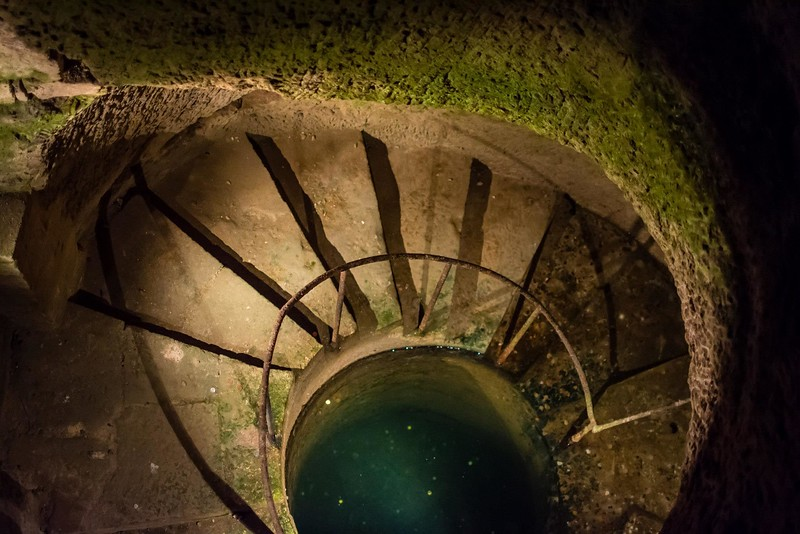 Spiral Staircase with water at the bottom - Paris Catacombs