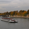 Tourist boat on the river Seine, Paris, France, with fall colors in the background.