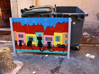 """In large and small towns garbage is collected in small dumpsters.  Small garbage trucks drive up and the garbage is carted off.  These dumpsters are often smelly and ugly looking.  I don't think I've ever seen """"art"""" used to hid dumpsters except in some of the towns of France that I have visited."""