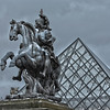 Statue in front of the glass pyramid at the Louvre Museum in Paris, France