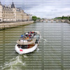 Tour boat filled with passengers gets ready to go under the Pont au Change Bridge by the Conciergerie Building.