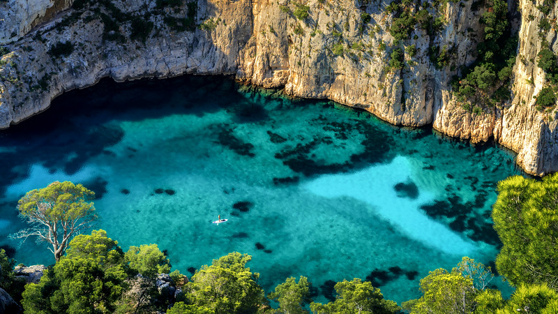 Morning view without people at Calanque d'En-Vau in Parc national des Calanques with sub board paddler