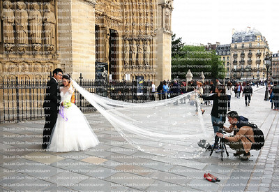 The demand for pre-wedding photographs at famous landmarks is a huge and lucrative business.  Asian couple takes pre-wedding photos in front of Notre Dame Cathedral.