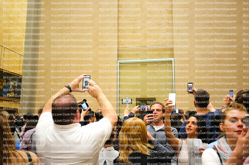 Large crowd at the Louvre Museum taking selfie photos with the Mona Lisa painting.