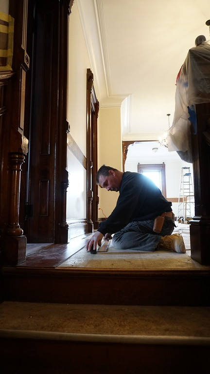 . Andy Frechette of Lowell installing new floors at the Franco American School. (The Sun / Chris Tierney)