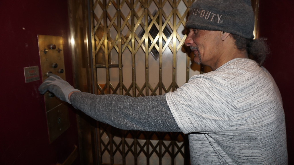. Abe Ramos of Lowell pushes the floor button in the elevator at Franco American School. (The Sun / Chris Tierney)