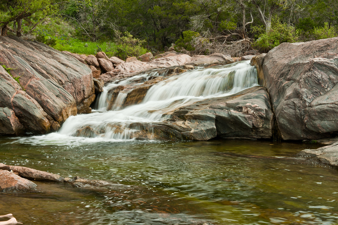 A small waterfall fed from a creek that runs into Inks Lake inside the state park.