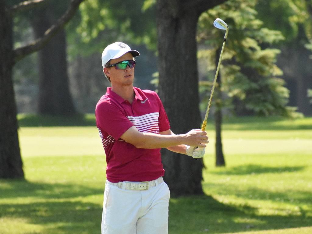 . Defending champion Jake Kneen watches his approach shot on the fourth hole Friday at the 50th annual Frank Syron Memorial Tournament at the Pontiac Country Club in Waterford Township. Kneen, from White Lake, recently won the Michigan Open. (The Oakland Press photo by Jason Schmitt)