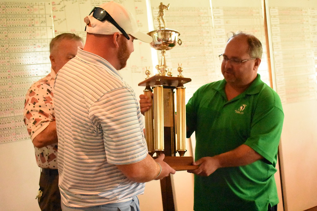 . Michael Syron (right) presents the Frank Syron Memorial Tournament trophy to Shelby Township\'s Connor Jones. The former Oakland University player shot a three day total of 205. (Digital First Media photo by Jason Schmitt)