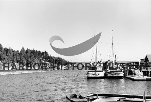Babich Boats Julia B and Invincible at dock while log boom towed nearby