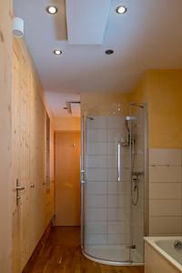 Bad EG mit Badewanne und Dusche, dahinter die Toilette