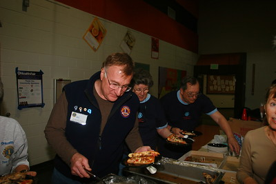 "From Left Bill Steinmiller, Cashier Supervisor, Joan VonderHeiden, Blood Pressure Supervisor and Ken VonderHeiden, Centrifuge Supervisor dig into some pizza from Winter Park Pizza Hut and some great  ""heart healthy"" food catered by the Devils Thumb Ranch.  Joan and Ken display the snazzy T-Shirt provided to all our volunteers."