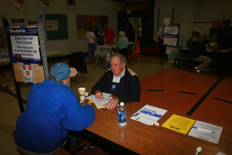 Fran Cassidy, Lions member, talks to a 9health Fair customer at Stop 2 where forms are checked.