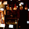 A meat market in Sicily of mostly cured ham.  With warm dry air the meat drys and cures fast.  A ham takes about 6 months to cure after it is soaked in Brine for a period of time.  It is then slice very thin and eaten as is.  No one ever has a problem with proccuto.