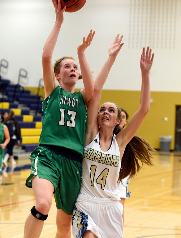 . Niwot High School\'s Mary Gillett drives to the hoop over Danielle Hemelstrand during a game against Frederick on Wednesday in Frederick. For more photos of the game go to BoCoPreps.com Jeremy Papasso/ Staff Photographer 11/29/2017