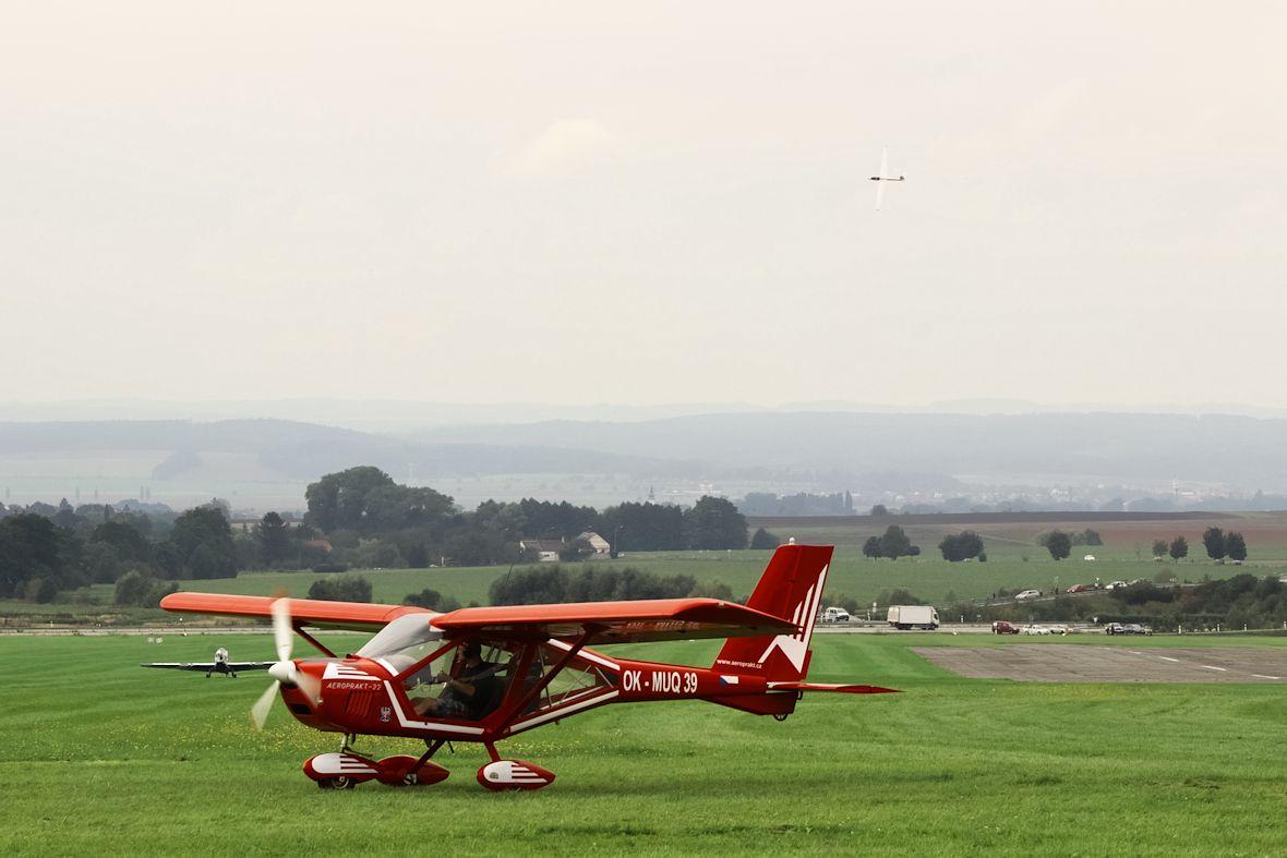 Na leteckých dnech je rušno - v pozadí přistává vlečná, v popředí se připravuje ke startu Aeroprakt 22, a ve vzduchu dokončuje sestavu Swift S1
