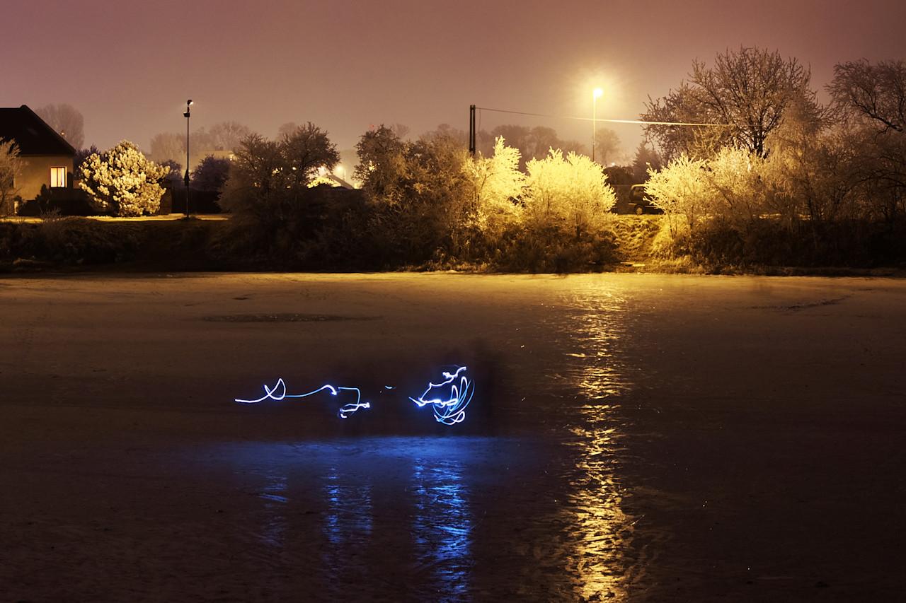 To není snaha o nezdařené kreslení světlem, to jsou prostě jenom lidé, klouzající se po ledě zamrzlého rybníku s baterkou v ruce ;)