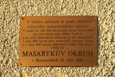 "The plaque says: ""On this very spot, motorsport history was being written. On Sunday 28th September 1930, Eliška Junková has done a honorary lap of the track as part of the very first automobile race at this track, and Antonin Vitvar in 1950 (first motorbike race on the track) and Phil Read in 1965 (first world championship) prepared here for their legendary wins. This is Masaryk Circuit. In Bosonohy, 28th September 2015."""