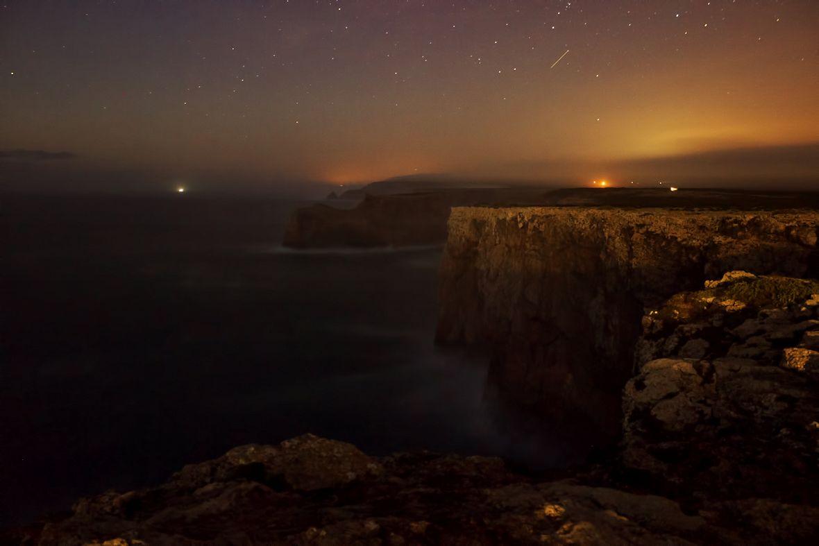 Pohled na pobřeží severně od Cabo de Sao Vicente, osvětlované září majáku...