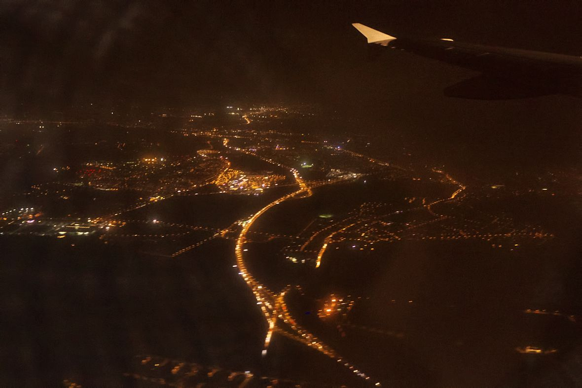 Někde zhruba nad Bořanovicemi se mezi mraky poprvé objevil výhled na večerní Prahu. Osvětlená silnice je výpadovka na Odolena vodu, Kralupy a tak dále.