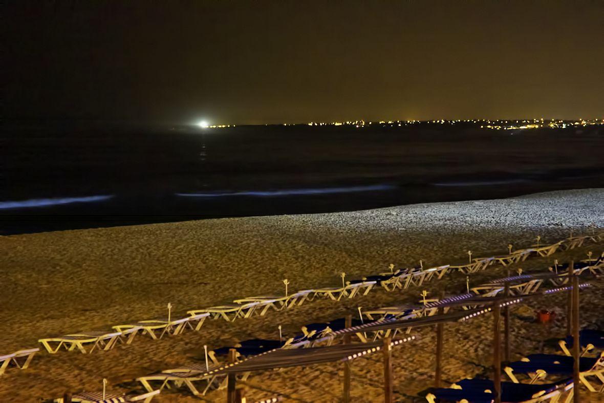 Snaha z terasy restaurace alespoň trochu zachytit paprsek majáku, přelétávající po krajině. Pravděpodobně se jednalo o maják u Benagilu, jehož záři jsem fotil už z útesů nad Praia da Marinha, vzdálený vzdušnou čarou zhruba deset kilometrů.