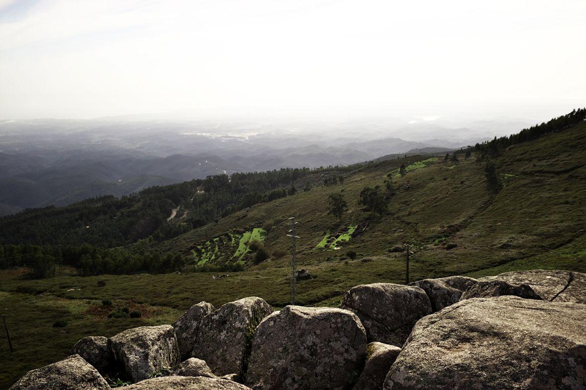 Pohled z vrcholku Foiy směrem zhruba na jihozápad. Přímo před námi areál okruhu v Algarve. Napravo od něj se leskne hladina nádrže Barragem de Odiaxére. Někde zhruba mezi nimi dál v oparu město Lagos.