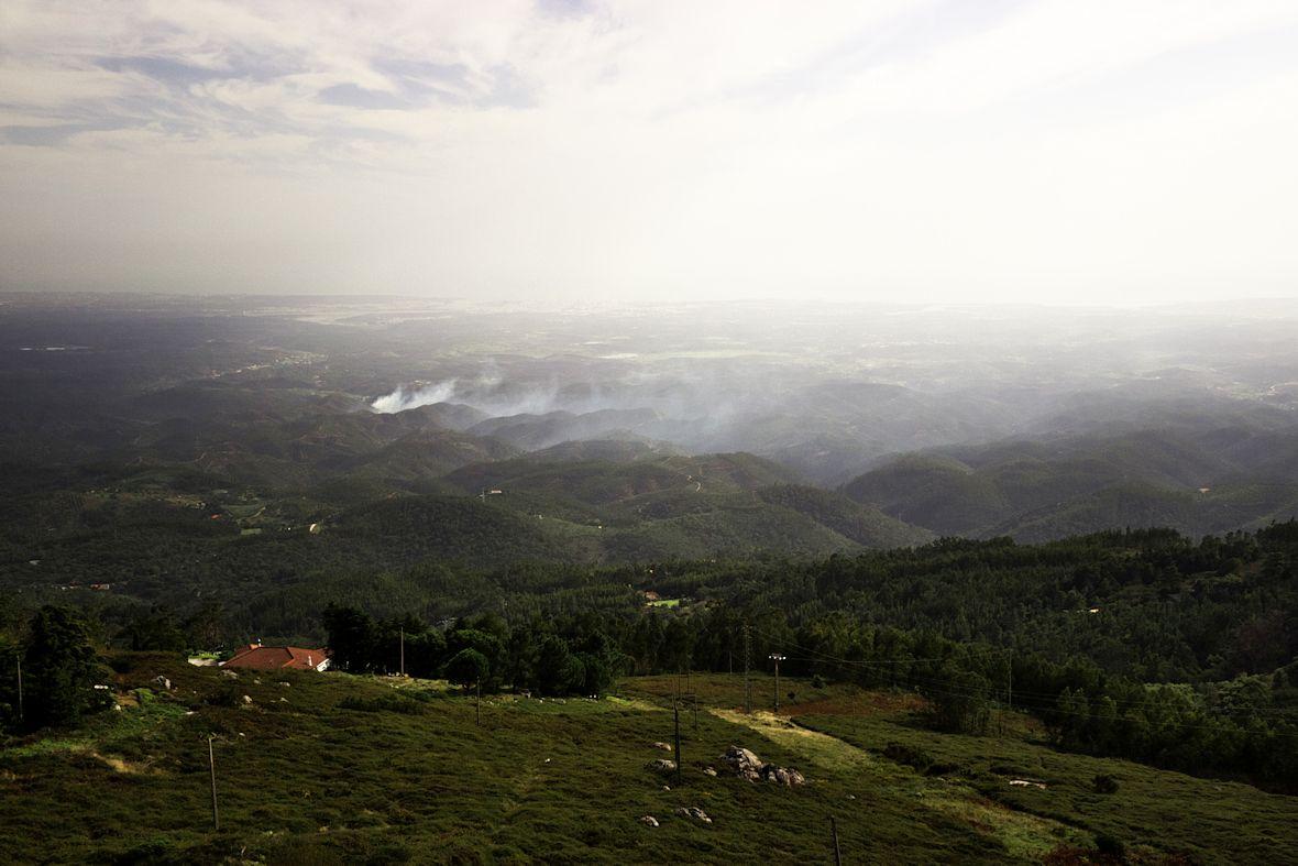 V dáli na pobřeží je vidět město Portimao, blíže evidentně nějaký lesní požár.